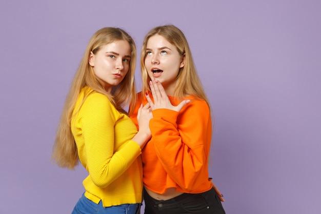 Due giovani sorelle gemelle bionde stupite in abiti colorati vividi in piedi, isolate sulla parete blu viola pastello. concetto di stile di vita familiare di persone.