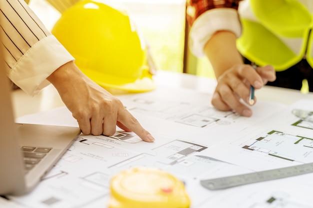 Due architetti-ingegneri si stanno consultando per modificare i progetti della casa appaltata, hanno un incontro per ispezionare i progetti della casa prima di incontrare il cliente. idee di design per la casa.