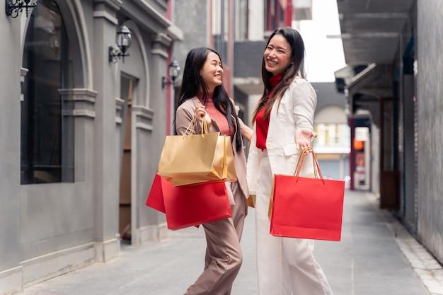 Due belle donne asiatiche con borse della spesa in città sopra il centro commerciale