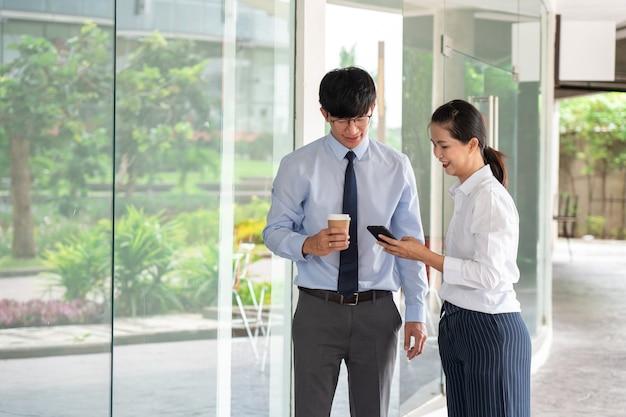 Due colleghi asiatici di affari fuori dagli edifici per uffici discutono e commentano il lavoro a vicenda.