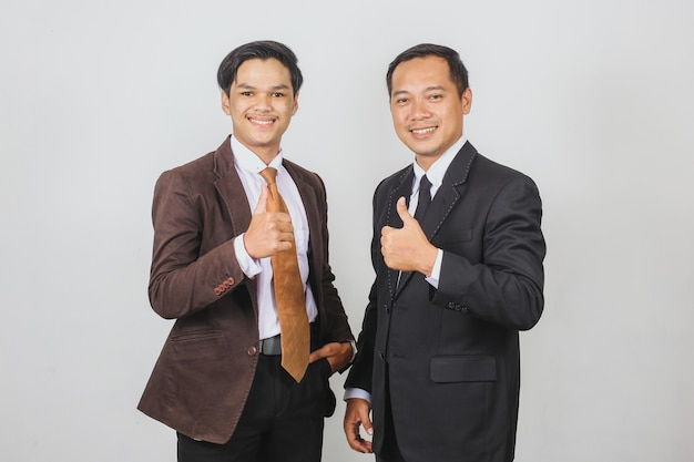 Due uomini d'affari asiatici in giacca e cravatta in posa insieme con il gesto del pollice in alto