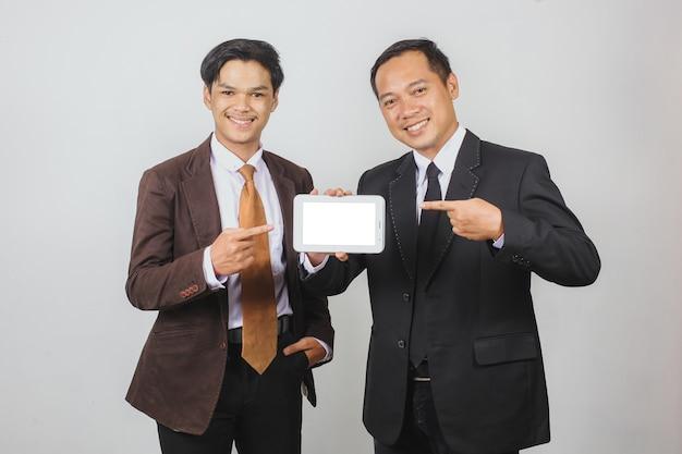 Due uomini d'affari asiatici in tuta che sorridono mentre puntano a uno smartphone con uno schermo vuoto per il mock up