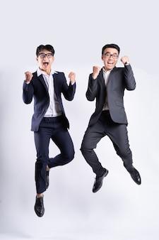 Due uomini d'affari asiatici che saltano su sfondo bianco