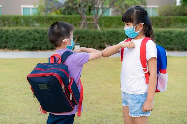 Due amici in età prescolare di bambini asiatici si incontrano nel parco della scuola invece di salutare con un abbraccio o una stretta di mano, si scontrano invece con i gomiti.