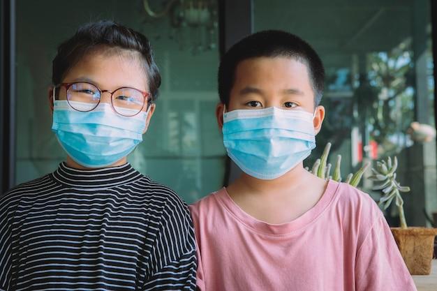 Due bambini asiatici che indossano la maschera per il viso di protezione in piedi a casa