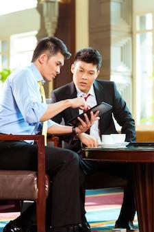 Due uomini d'affari cinesi asiatici o persone in ufficio che hanno una riunione di lavoro nella hall di un hotel discutendo documenti su un tablet pc mentre beve il caffè