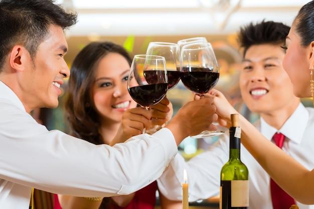 Due coppie asiatiche cinesi o amici o uomini d'affari che tostano durante la cena o il pranzo in un elegante ristorante con bicchieri di vino rosso