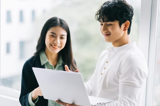 Due colleghi asiatici stanno discutendo del lavoro. l'uomo d'affari tiene in mano un computer portatile