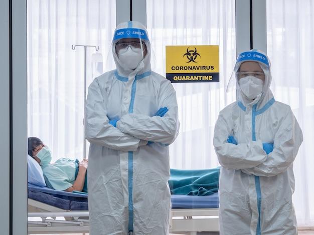 Due medici asiatici indossano tuta in dpi con maschera n95 e visiera, trattano il paziente infetto da coronavirus nella sala a pressione negativa, etichetta con segno di zona di allarme di quarantena.