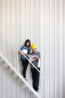 Due ingegneri asiatici, uomo e donna, discutono in cantiere