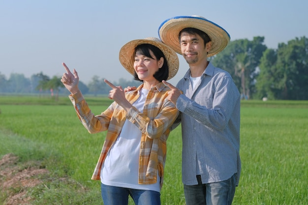 Due contadini asiatici sorridono e posano il dito puntato contro la fattoria verde
