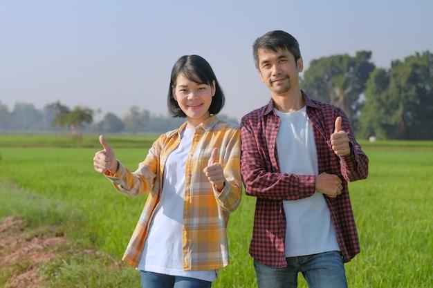 Due agricoltori asiatici in piedi e pollice in alto alla fattoria di riso verde. concetto di coppia di agricoltori. Foto Premium
