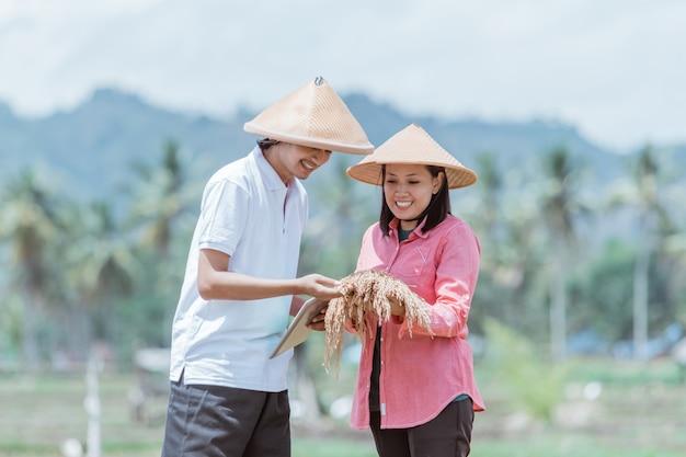 Due contadini asiatici che indossano cappelli si sentono felici in possesso di una bella pianta di riso mentre stanno con una compressa nelle risaie