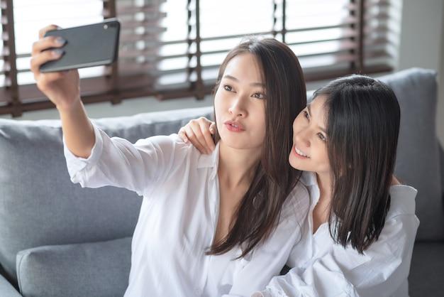 Due donne asiatiche utilizzando il telefono cellulare e la tecnologia internet per utilizzare la videochiamata ad altri amici durante il soggiorno al sicuro a casa