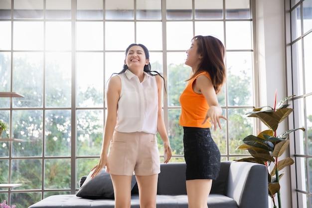 Due amiche asiatiche che ballano nel soggiorno a casa, donna felice rimanere a casa