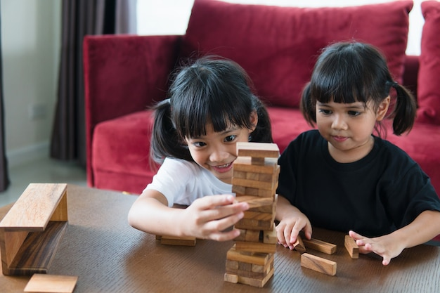 Due ragazze asiatiche che giocano a pile di legno a casa