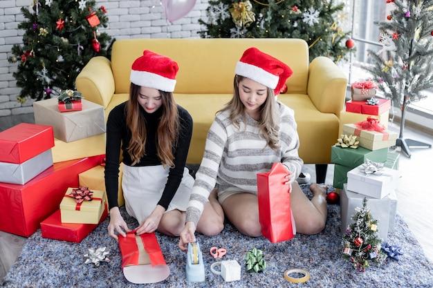 Due ragazze asiatiche hanno avvolto un regalo per natale