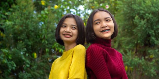 Due ragazze giovani felici asiatiche in natura