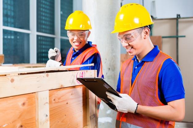 Due operai industriali o edili indonesiani asiatici controllano con una lista di controllo una consegna su un cantiere a torre e aprono una scatola di legno o un container con un piede di porco