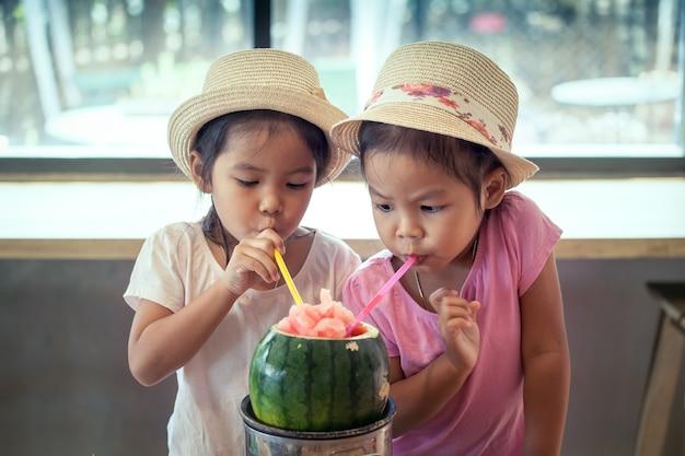 Due bambine asiatiche stanno bevendo succo di anguria mescolato insieme nel ristorante