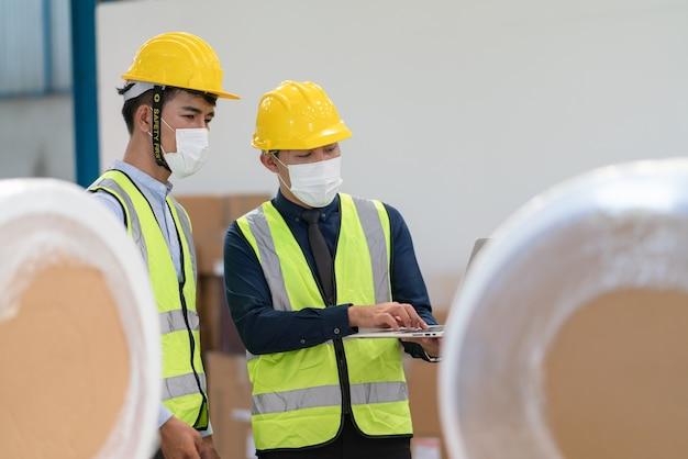 Due ingegneri maschi asiatici indossano una maschera utilizzando il computer portatile che controlla la qualità del prodotto presso la fabbrica del magazzino