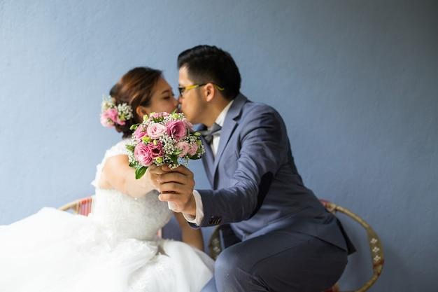 Due persone asiatiche che si baciano dietro il bouquet il giorno di san valentino