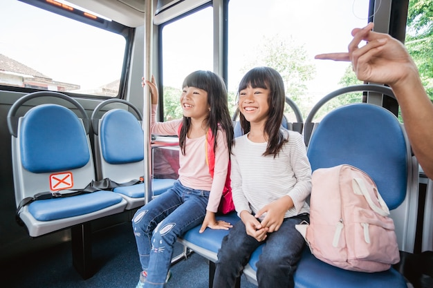 Due studenti primari asiatici che vanno a scuola in autobus con i mezzi pubblici