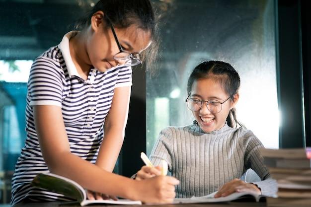 Due studenti asiatici leggendo un libro di scuola con emozione di felicità