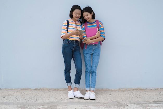 Una ragazza giovane dell'allievo due asiatici che osserva computer portatile alla scuola sulla parete blu