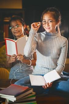 Due adolescenti asiatici e booket in mano seduti in biblioteca
