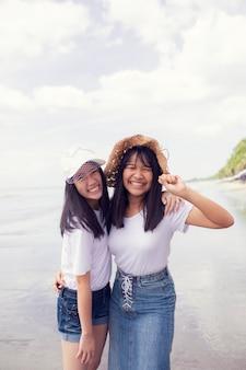 Due felicità asiatica dell'adolescente sulla spiaggia del mare