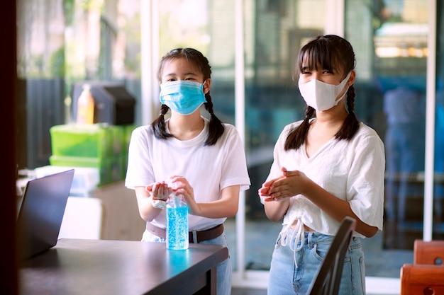 Due adolescenti asiatici lavarsi le mani con gel alcolico