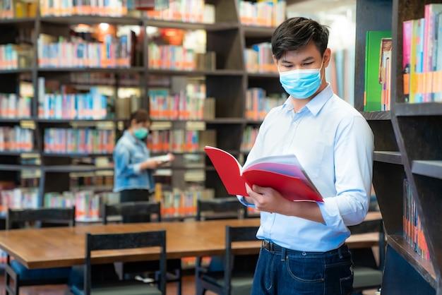 Due studenti universitari asiatici che indossano la maschera per il viso in biblioteca