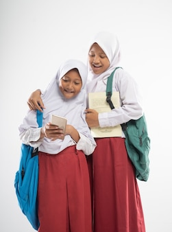 Due ragazze asiatiche velate che indossano uniformi scolastiche elementari usano uno smartphone insieme quando trasportano ...