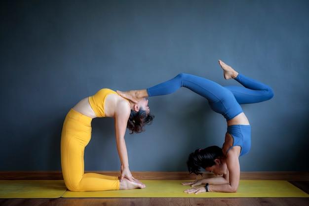 Una donna asiatica due che fa posa di yoga dentro sul pavimento