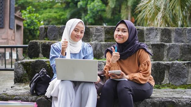 Due amici asiatici della studentessa che discutono con il gesto giusto
