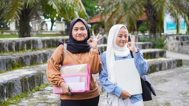 Un amico di due studenti asiatici della donna che cammina sulla città universitaria con il gesto giusto