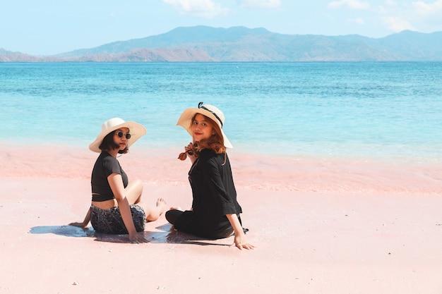 Due donne asiatiche in cappello estivo seduto e guardando la telecamera in spiaggia di sabbia rosa a labuan bajo