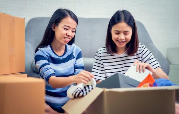 Una donna di due asiatici che disimballa unboxing varie cose dal trasloco della nuova casa.