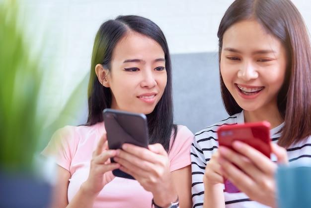 Una donna di due asiatici che per mezzo dello smartphone sul tempo di vacanza e si diverte usando la tecnologia insieme.