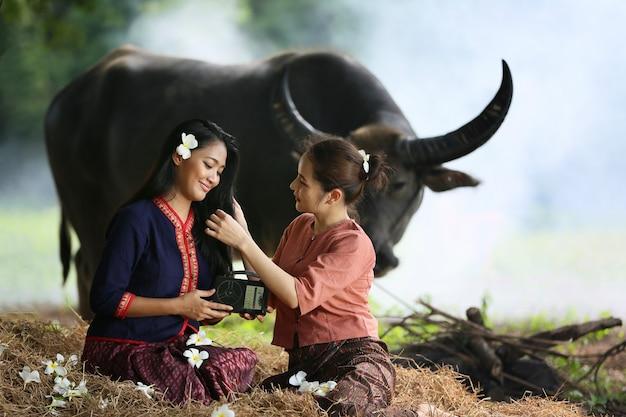 Due donna asiatica che indossa il costume tradizionale tailandese seduto in campo, mentre si ascolta la radio in stile vintage accanto al bufalo