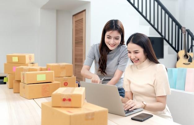 Due donne asiatiche stanno guardando i loro computer portatili per controllare gli ordini, con scatole di cartone e borse della spesa tutt'intorno