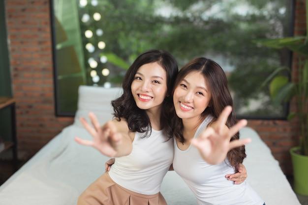 Due donne asiatiche in camera da letto sul letto si divertono