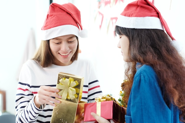 Due donne asiatiche che tengono il contenitore di regalo con felicità nella festa di natale