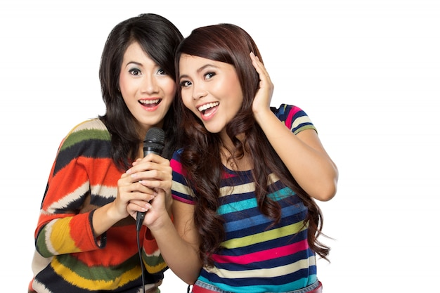 Due donne asiatiche in maglietta a strisce cantando insieme