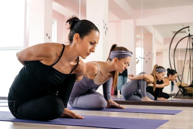 Due giovani donne atletiche in abiti sportivi che fanno yoga posa sulla stuoia in palestra