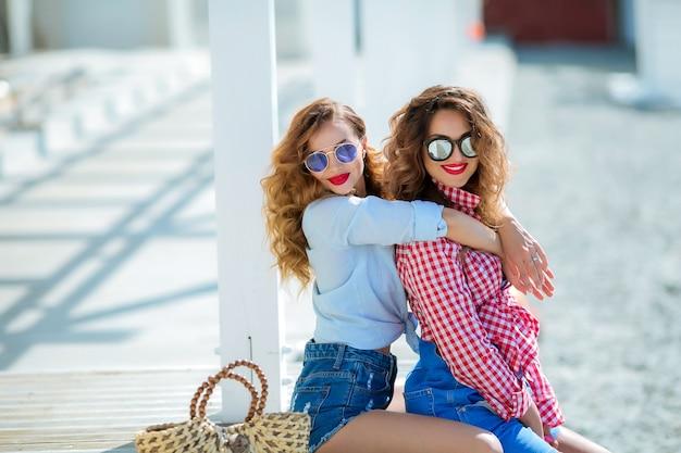 Due ragazze attraenti, allegre migliori amiche che si divertono alla festa in spiaggia. indossa abiti estivi, pantaloncini e magliette, divertendoti alla moda con bei capelli mossi. isolated.hat e occhiali da sole
