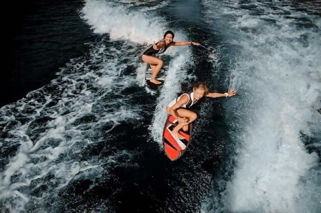 Due ragazze attraenti a cavallo sul wakeboard sul lago