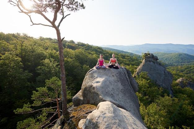 Due ragazze attraenti siedono meditando nella posa del loto, illuminata dal sole estivo, sulla cima di un'enorme roccia sulla foresta di montagna