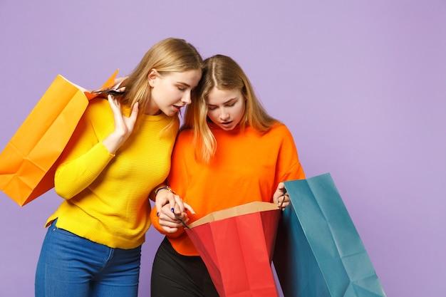 Due giovani sorelle gemelle bionde attraenti in abiti vivaci tengono la borsa del pacchetto con gli acquisti dopo lo shopping isolato sulla parete blu viola. concetto di stile di vita familiare di persone.